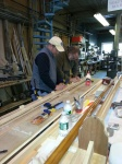 "Tim Greves and Bill Lawton have placed the side on the ""keel-blocks"" and are gluing temporary rectangular blocks in place at the stations ensuring that the top will bend to the edge of the side at right angles."