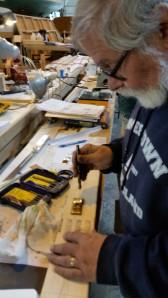 9. Steve prepares metal traveler pads and teak bases